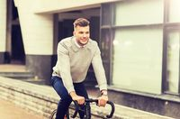 young man riding bicycle on city street