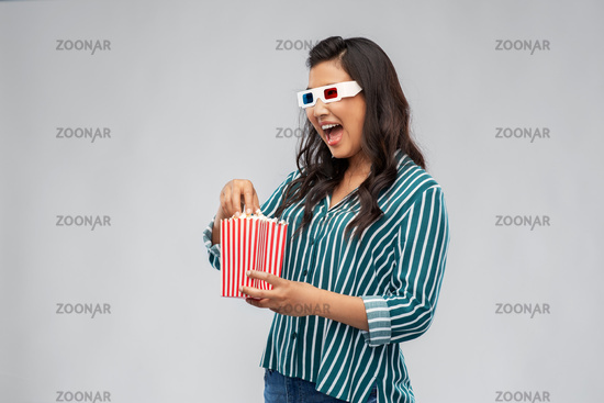 asian woman in 3d movie glasses eating popcorn