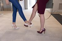 Low section of two businesswomen greeting each other by touching feet at modern office