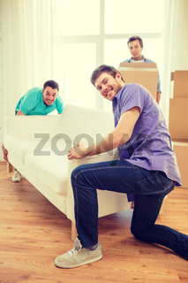 smiling friends with sofa and boxes at new home