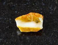 unpolished yellow Amber gemstone on black