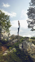 Woman practicing yoga on top rocky mountain