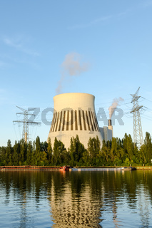 Cooling tower of a coal-fired power station with electricity pylons and supply with ships