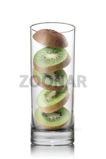 falling kiwi slices inside glass isolated