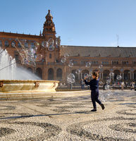 Little girl play with flying soap bubbles, Plaza de España, Sevilla, Spain