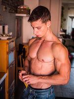 Shirtless muscular young man eating cereal bar, looking at camera standing,