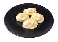 cooked Manti on black plate isolated on white
