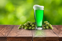 Still life with glass of fresh green beer and hops.