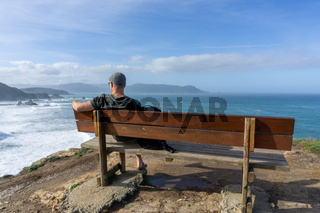 man relaxing and enjoying the vie at the cliffs of Loiba in Galicia