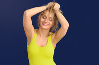 Happy carefree blond woman with hands to hair
