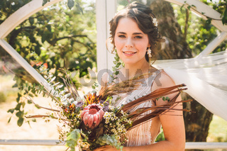 Beautiful bride with bouquet flowers stands on forest background. Rustic style. beautiful bride in delicate dress outdoors. Close up portrait of young bride in park in sunny weather wooded area
