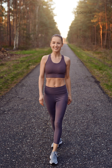 Smiling athletic fit young woman working out