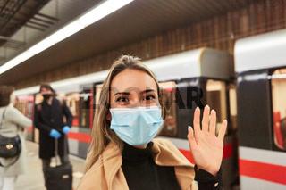 Pendlerin mit Maske wegen Covid-19 winkt zur Begrüßung