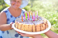 Holiday homemade cake in close-up hands. Smiling grandmother is holding a birthday homemade cake. Family celebrating grandmother's birthday