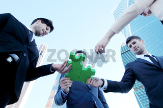 Business people put puzzle together