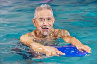 Senior mit Schwimmbrett im Wasser