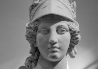 Greek ancient statue of goddess Athena. Woman marble head in helmet sculpture