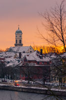 The tower of the church St. Mang in Regensburg on the danube river on cold winter morning in December with fresh snow on the roofs