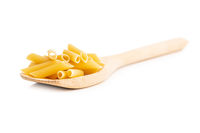 Uncooked penne pasta. Dried italian pasta in wooden spoon