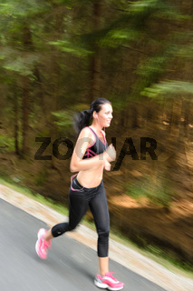 Young woman running outdoors motion blur