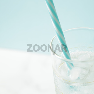 glass with ice cubes on white table
