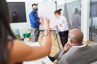 Business Team mit Maske im Strategie Workshop