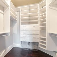 Square Fully fitted empty white walk-in wardrobe bright interior