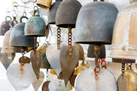 Many small metal bells hanging in Buddhist temple
