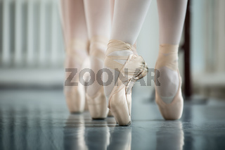 Legs dancers on white pointe, near the choreographic training ma