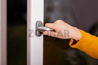 Woman opens the window to ventilate