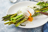 Green asparagus with poached egg and parmesan, vegetarian breakfast served on two white plate on light background.