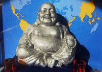 statue of Buddha in front of world map