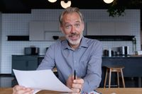 Caucasian businessman sitting having video chat going through paperwork in modern office
