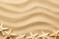 Starfishes On Wavy Sand Background