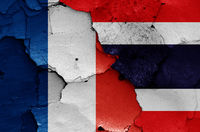 flags of France and Thailand painted on cracked wall