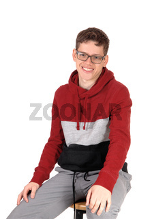 Smiling teenager sitting on a chair in a sweater