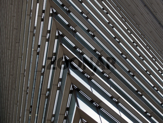 close up detail of the corner of a large modern office building with geometric metallic steel lines