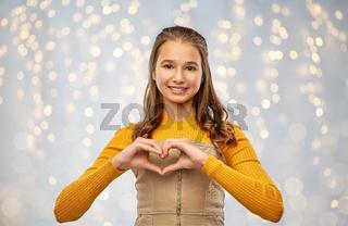 smiling teenage girl making hand heart