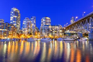 Vancouver BC skyscrapers and Granville Bridge reflection along False Creek at blue hour