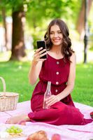 happy woman with smartphone and drink at park