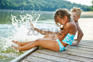 Kinder plantschen im Wasser im Sommer