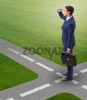 The young businessman at crossroads in uncertainty concept