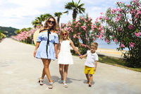 Young beautiful mother walking her little son and daughter outdoors. Mom and kids having fun together in green garden by the sea