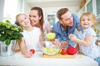 Glückliche Familie mit Salat in der Küche
