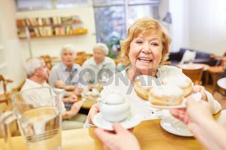 Seniorin holt sich frische Pfannkuchen für die Kaffeerunde im Seniorencafe