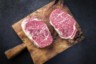 Raw dry aged wagyu entrecote beef steak roast as top view on a rustic wooden cutting board