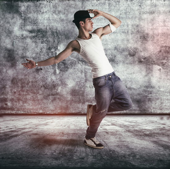 Hip young man in a tank top and hat doing a dance routine posing on one leg in a grunge concrete room or stage