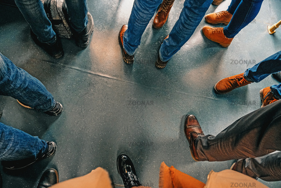 Human feet in circle in shoes and jeans. Close up view of people in a bus standing with luggage driving in airport. Top view