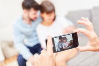 Smartphone macht Foto von Eltern mit Baby