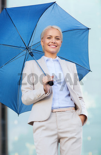 young smiling businesswoman with umbrella outdoors
